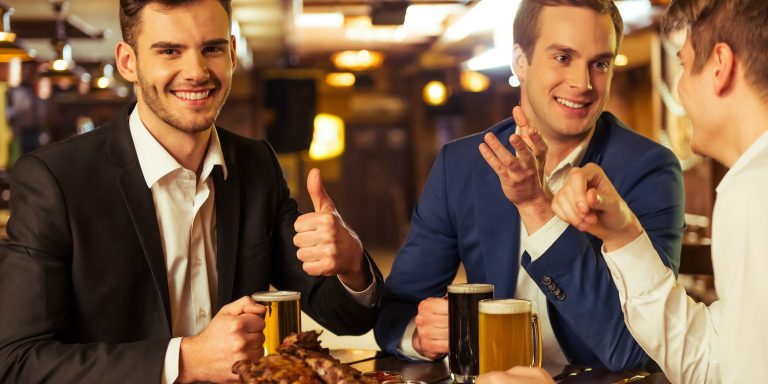 Three young businessmen in suits are smiling, talking and drinking beer while sitting in pub, dark haired man is showing Ok sign